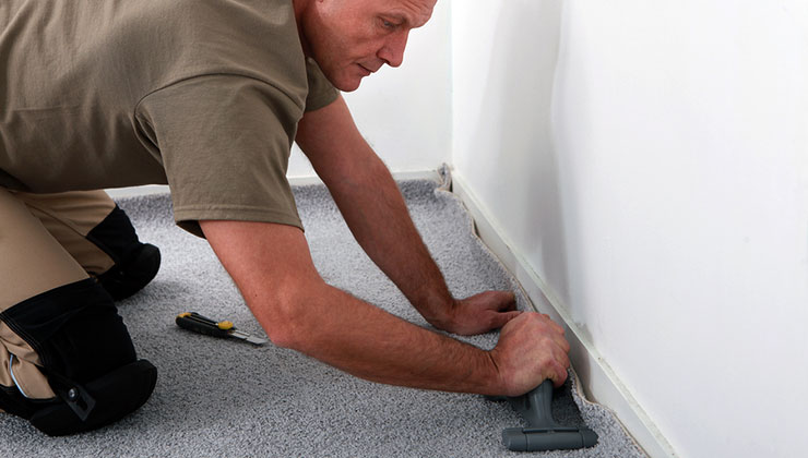 Photo of carpet installer at work.