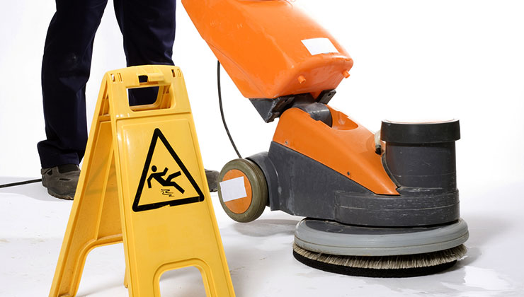 Worker using a floor cleaning machine.